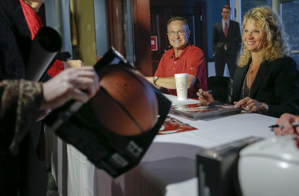 Photo - University of Oklahoma men's and women's basketball coaches Lon Kruger and Sherri Coale  signs autographs for fans during the Sooner Caravan at the Jim Thorpe Museum in Oklahoma City, Okla. on Wednesday, July 30, 2014.  Photo by Chris Landsberger, The Oklahoman