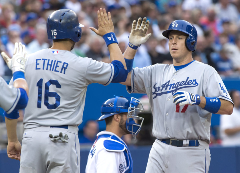 Photo - Los Angeles Dodgers A.J. Ellis celebrates his two-run homerun with teammate Andre Ethier as Toronto Blue Jays catcher J.P. Arencibia looks on during the second inning against the Toronto Blue Jays  in Toronto on Monday July 22, 2013. (AP Photo/The Canadian Press, Frank Gunn)