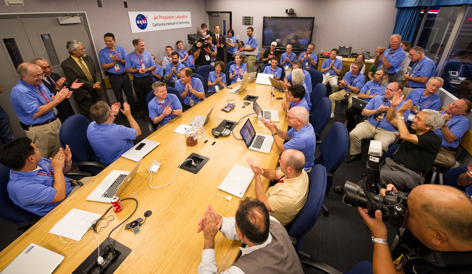 Photo -   In this photo provided by NASA, the Mars Science Laboratory (MSL) team welcomes White House Science and Technology Advisor John Holdren, third standing from left, as he stops by to meet the landing team and to say