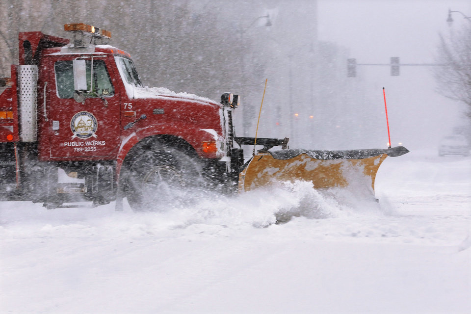 Photo - A city snow plow clears a street of snow in an almost deserted downtown as strong winds and snow move through the Midwest, Sunday, Jan. 5, 2014, in Springfield, Ill. Temperatures not seen in years are likely to set records in the coming days across the Midwest, Northeast and South, creating dangerous travel conditions and prompting church and school closures. (AP Photo/Seth Perlman)