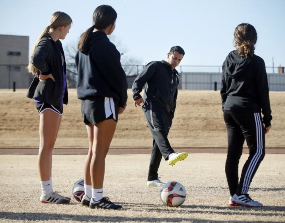 Photo -  Johnny Charqueño, an English-learner teacher and assistant girls' soccer coach at Northwest Classen High School, instructs students on kicking technique during the seventh-hour soccer class recently. [Nate Billings/The Oklahoman]