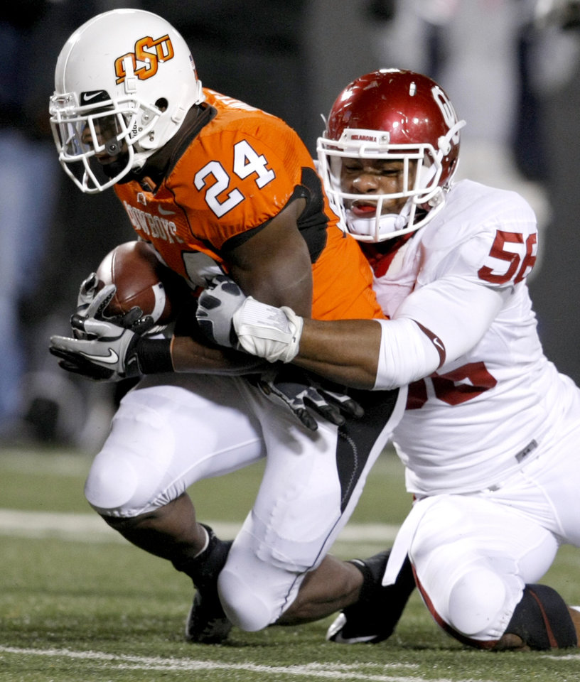 Photo - Oklahoma's Ronnell Lewis (56) brings down Oklahoma State's Kendall Hunter (24) during the Bedlam college football game between the University of Oklahoma Sooners (OU) and the Oklahoma State University Cowboys (OSU) at Boone Pickens Stadium in Stillwater, Okla., Saturday, Nov. 27, 2010. Photo by Bryan Terry, The Oklahoman