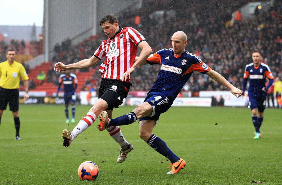 Photo - Sheffield United's Chris Porter, left, and Fulham's Philippe Senderos battle for the ball during their FA Cup, Fourth Round soccer match at Bramall Lane, Sheffield, England, Sunday Jan. 26, 2014. (AP Photo/PA, Nick Potts) UNITED KINGDOM OUT  NO SALES  NO ARCHIVE