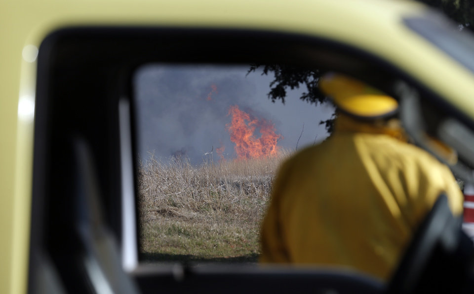Photo - A firefighter watches flames burns near East Seward Road and Oak Hill Road,  Sunday, May 4, 2014. Photo by Sarah Phipps, The Oklahoman