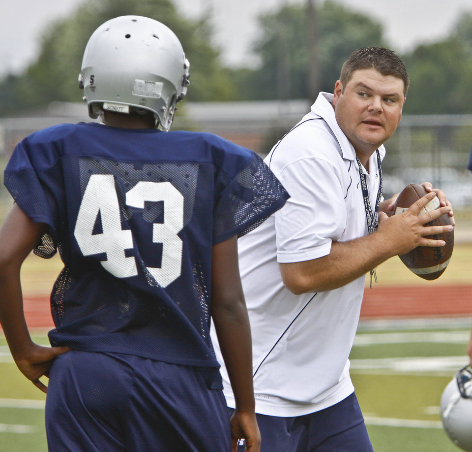 Head coach Jeremy Dombek goes over quarterback drills with his squad during the Edmond North football practice on Tuesday, Aug. 24, 2010, in Oklahoma City, Okla. The Huskies are preparing for their season opening game against Southmoore.   Photo by Chris Landsberger, The Oklahoman Archives