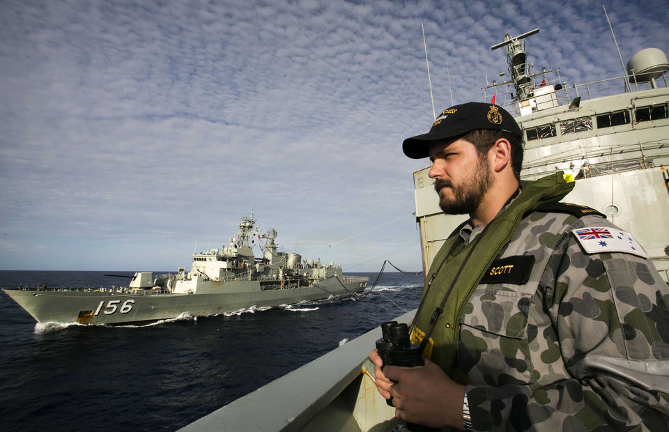 Photo - In this April 7, 2014 photo provided by the Australian Defence Force Able Seaman Steward Kirk Scott keeps watch on deck of HMAS Success as they conduct a replenishment at sea with HMAS Toowoomba, left, while both ships are deployed in the search of the missing Malaysia Airlines Flight 370 in the southern Indan Ocean. Authorities are confident that a series of underwater signals detected in a remote patch of the Indian Ocean are coming from the missing Malaysia Airlines plane's black boxes, Australia's prime minister said Friday, April 11. (AP Photo/Australian Defence Force, Julianne Cropley) EDITORIAL USE ONLY