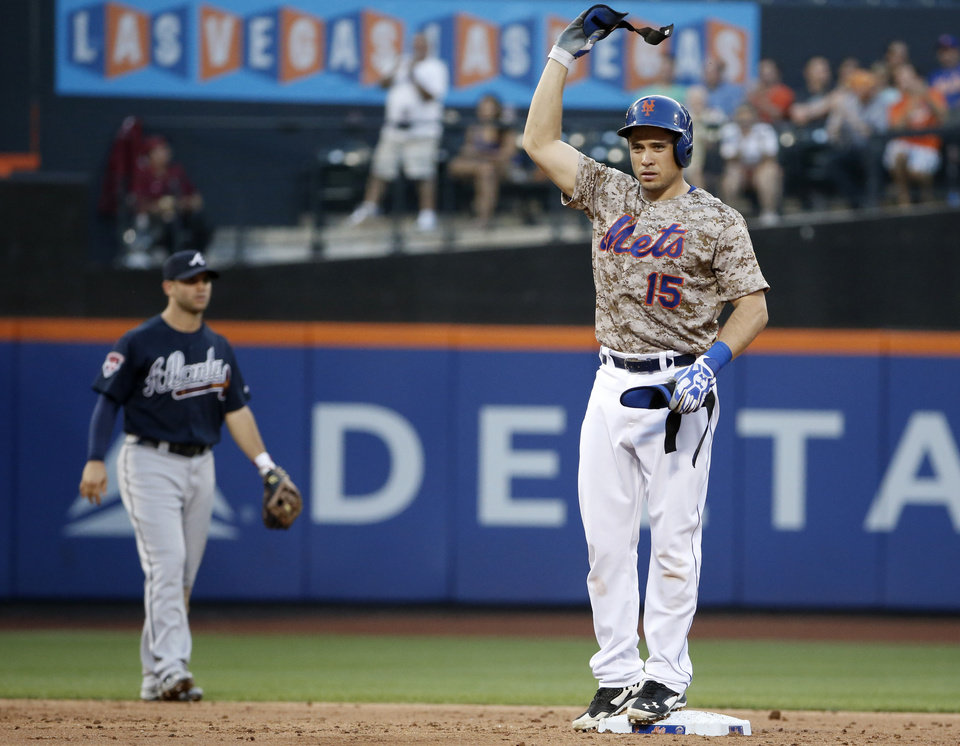 Photo - New York Mets Travis d'Arnaud waves his batting gear over his head after hitting a run-scoring, second-inning, double off Atlanta Braves starting pitcher Mike Minor  in a baseball game in New York, Monday, July 7, 2014. (AP Photo/Kathy Willens)