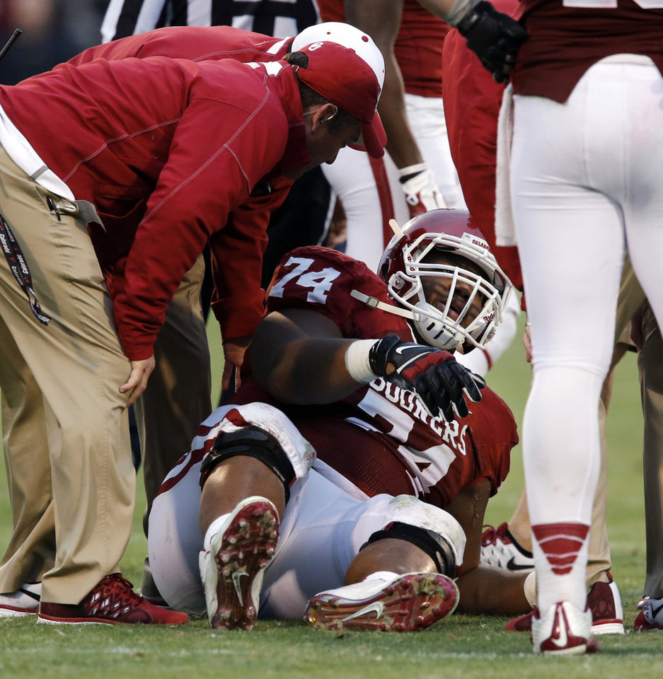 Photo - Staff attend to Sooner's Adam Shead (74) during the second half of a Bedlam college football game between the University of Oklahoma Sooners (OU) and the Oklahoma State Cowboys (OSU) at Gaylord Family-Oklahoma Memorial Stadium in Norman, Okla., on Saturday, Dec. 6, 2014. Photo by Steve Sisney, The Oklahoman
