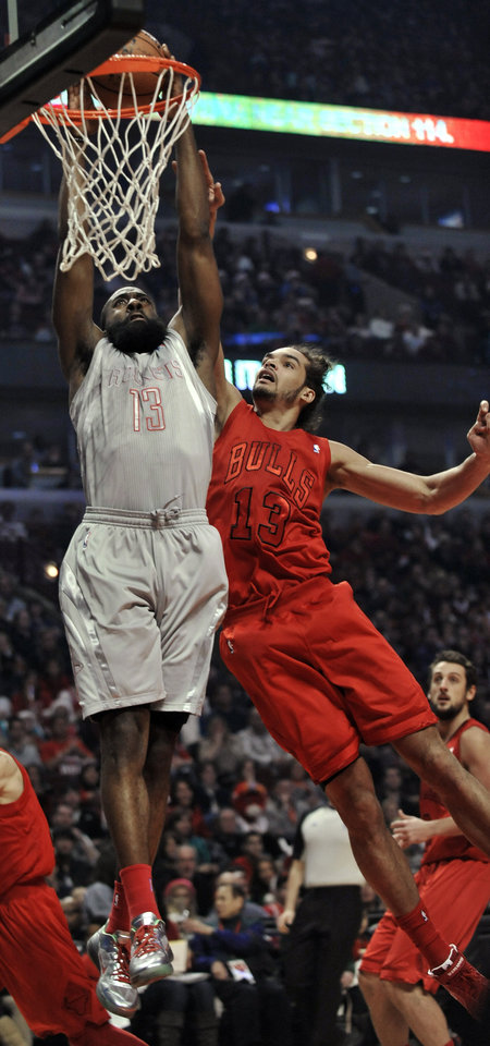 Houston Rockets\' James Harden, left, dunks over Chicago Bulls\' Joakim Noah during the first quarter of an NBA basketball game in Chicago, Tuesday, Dec. 25, 2012. (AP Photo/Paul Beaty)