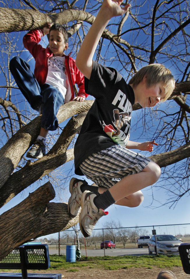 Jakey Stanley, 8, (right) jumps from a tree as he and Sean Bernd-Knighton, 8, enjoy the unusually warm weather on Friday, Dec. 30, 2011, in Norman, Okla.  Photo by Steve Sisney, The Oklahoman