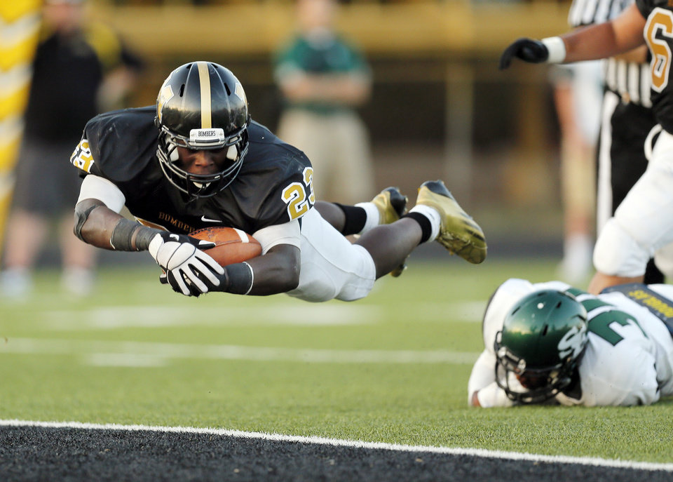 Midwest City\'s Qualan Johnson (23) leaps for a touchdown during the high school football game between Midwest City and Edmond Santa Fe at Rose Field in Midwest City, Okla., Thursday, Aug. 30, 2012. Photo by Nate Billings, The Oklahoman