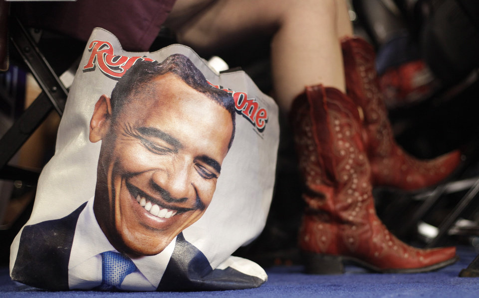 Photo - Colorado delegate Tracy Ducharme from Colorado Springs wears cowboy boots as she sit next to her bag showing President Barack Obama during the Democratic National Convention in Charlotte, N.C., on Tuesday, Sept. 4, 2012. (AP Photo/David Goldman)  ORG XMIT: DNC767