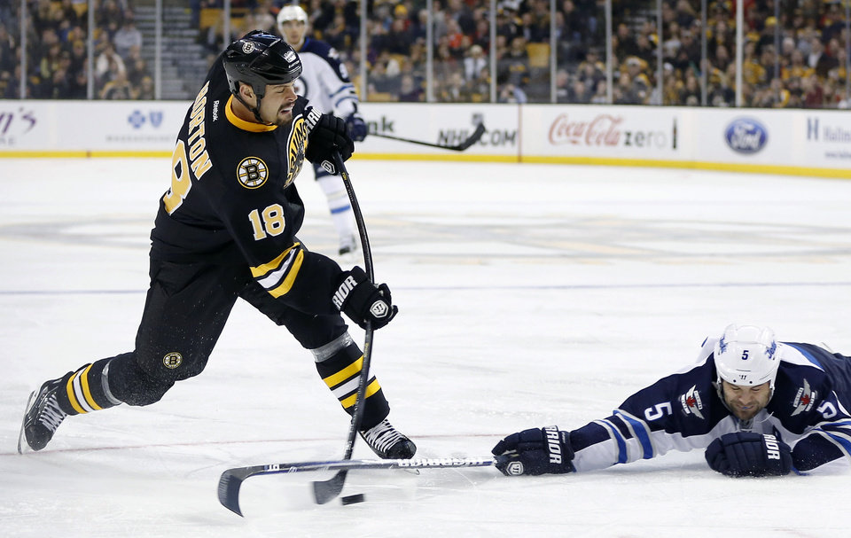 Photo - In this Jan. 21, 2013, file photo, Boston Bruins' Nathan Horton (18) shoots as Winnipeg Jets' Mark Stuart defends during an NHL hockey game in Boston. Horton, a 28-year-old, playoff-hardened free-agent right wing, signed a seven-year deal on Friday, July 5, 2013, worth $37.1 million with the Columbus Blue Jackets. He left the Bruins, with which he won the 2011 Stanley Cup and went to the finals this year. (AP Photo/Michael Dwyer, File)