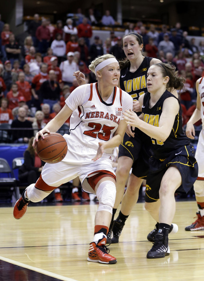 Photo - Nebraska forward Emily Cady, left, drives against Iowa guard Samantha Logic in the second half of an NCAA college basketball game in the finals of the Big Ten women's tournament in Indianapolis, Sunday, March 9, 2014. Nebraska defeated Iowa 72-65. (AP Photo/Michael Conroy)