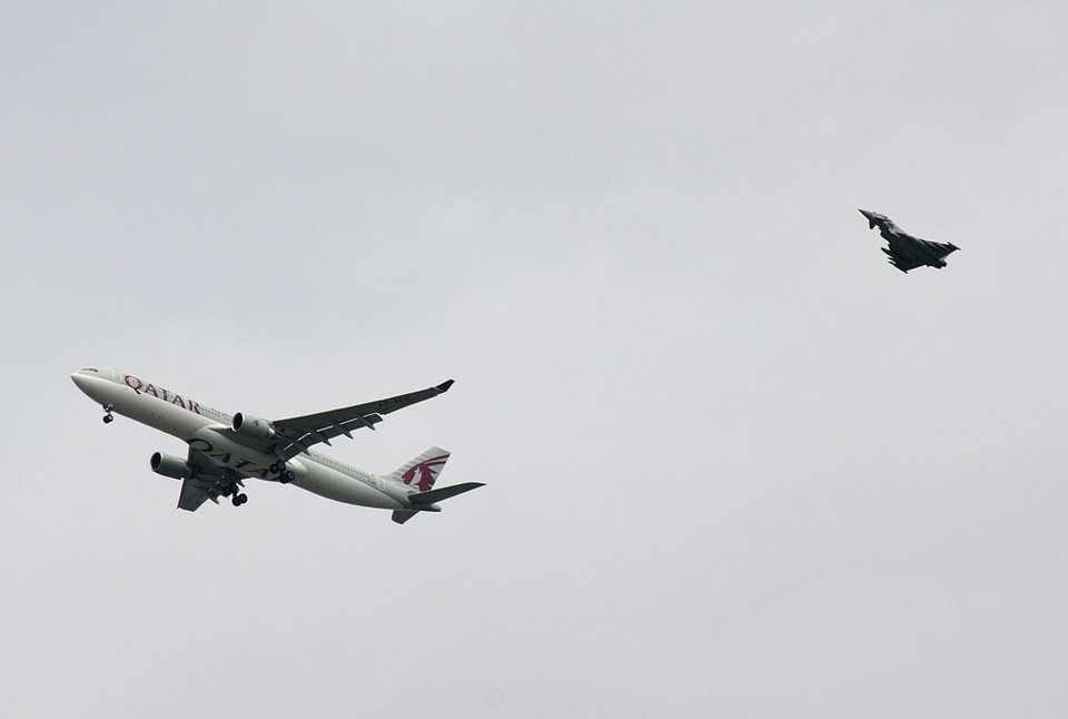 Photo - A military fighter jet escorts a passenger jet as it comes in to land at Manchester airport, Manchester, England, Tuesday, Aug. 5, 2014. Police say they have arrested a man on suspicion of making a hoax bomb threat after Qatar Airways Flight 23 landed with a military fighter escort at Britain's Manchester Airport. (AP Photo/Matthew Cossar)