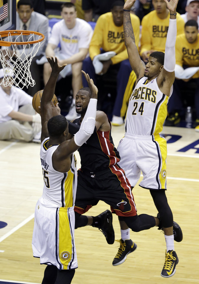Photo - Miami Heat's Dwyane Wade (3) goes makes a pass against Indiana Pacers' Roy Hibbert (55) and Paul George during the second half of Game 3 of the NBA Eastern Conference basketball finals in Indianapolis, Sunday, May 26, 2013. (AP Photo/Michael Conroy)