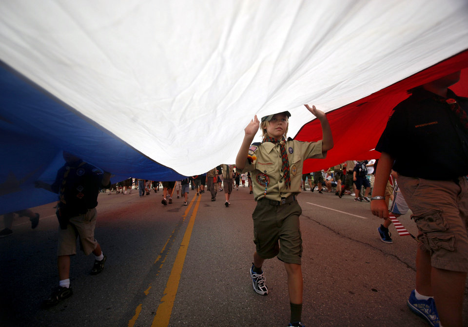Photo - Boy Scouts of America and Cub Scout troops carry a large American Flag during the LibertyFest Parade in Edmond, Okla., Monday, July 4, 2011. Photo by Sarah Phipps, The Oklahoman