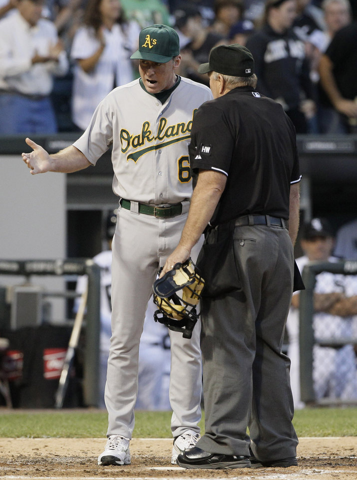 Photo -   Oakland Athletics manager Bob Melvin, left, argues with home plate umpire Bob Davidson during the fourth inning of a baseball game against the Chicago White Sox in Chicago, Saturday, Aug. 11, 2012. (AP Photo/Nam Y. Huh)