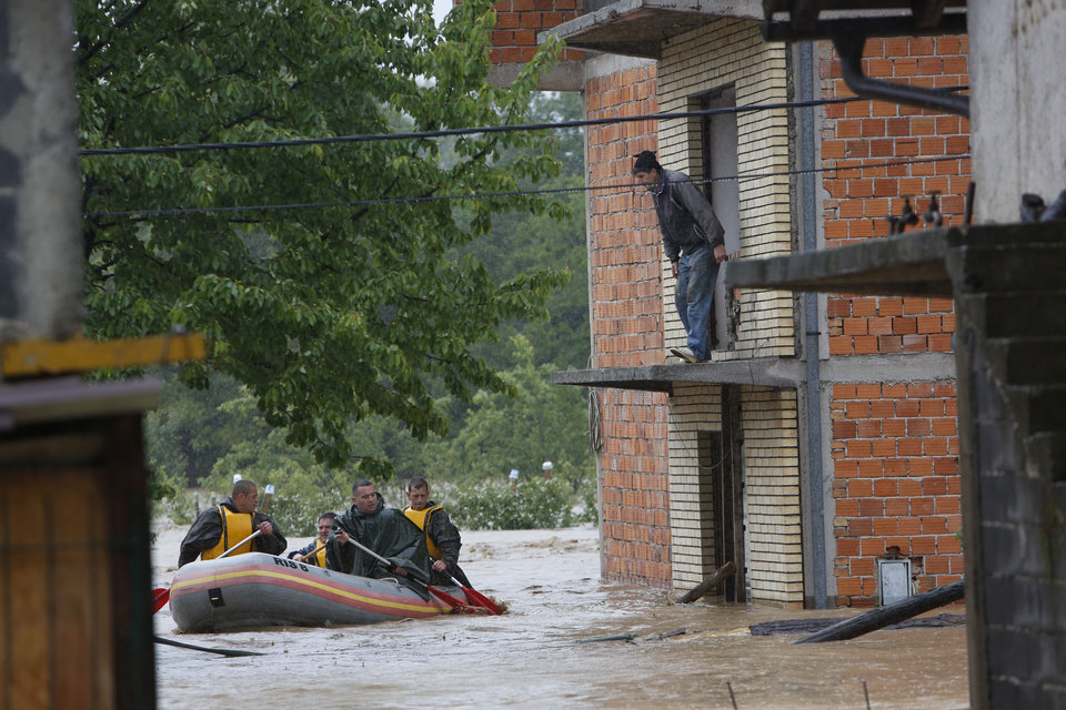 Photo - Bosnian Army paddle to rescue a person from a house near Zepce, 120 kms north of Sarajevo, Thursday May 15, 2014. Heavy rainfall caused the river Bosna to flood surrounding areas causing power cuts and road blockades in some suburban and rural areas. (AP Photo/Amel Emric)