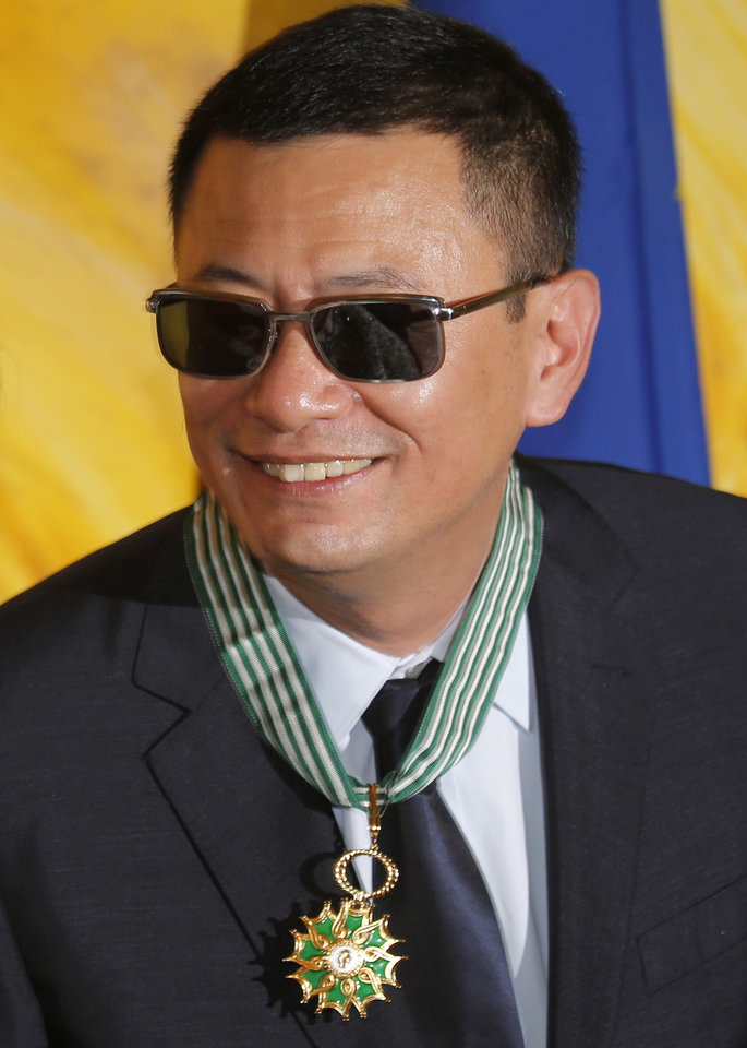 Photo - Hong Kong director Wong Kar-wai smiles after he received the Commandeur des Arts et Lettres from French Foreign Minister Laurent Fabius, in Hong Kong Sunday, May 5, 2013. Wong has been given France's highest cultural honor. (AP Photo/Vincent Yu)
