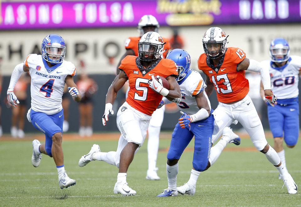 Photo - Oklahoma State's Justice Hill (5) rushes as Boise State's DeAndre Pierce (4) and Evan Tyler (5) defend in the third quarter during a college football game between the Oklahoma State Cowboys (OSU) and the Boise State Broncos at Boone Pickens Stadium in Stillwater, Okla., Saturday, Sept. 15, 2018. OSU won 44-21. Photo by Sarah Phipps, The Oklahoman