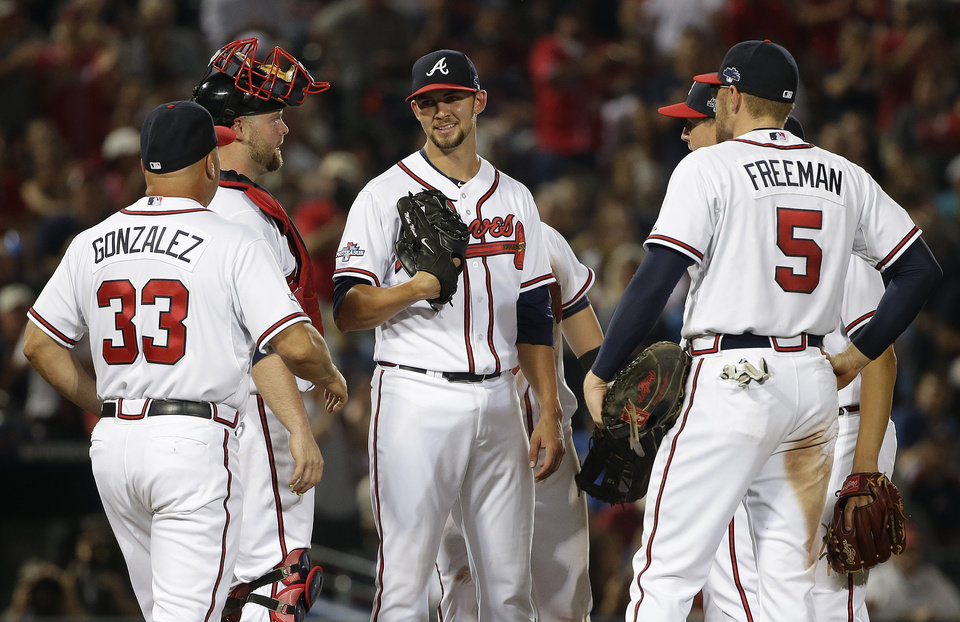 Atlanta Braves starting pitcher Mike Minor, center, speaks to catcher Brian McCann, second from left, and other teammates in the seventh inning during Game 2 of the National League division series against the Los Angeles Dodgers, Friday, Oct. 4, 2013, in Atlanta. (AP Photo/John Bazemore)