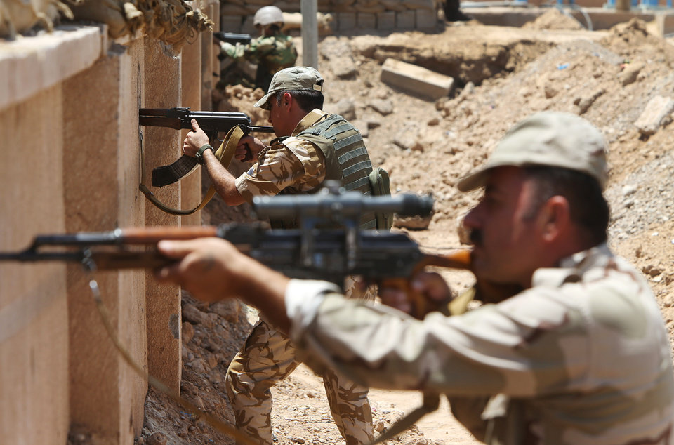 Photo - Kurdish peshmerga fighters take their positions behind a wall on the front line with militants from the al-Qaida-inspired Islamic State in Iraq and the Levant (ISIL), in Tuz Khormato, 100 kilometers (62 miles) south of the oil rich province of Kirkuk, northern Iraq, Wednesday, June 25, 2014. A defiant Prime Minister Nouri al-Maliki rejected calls Wednesday for an interim
