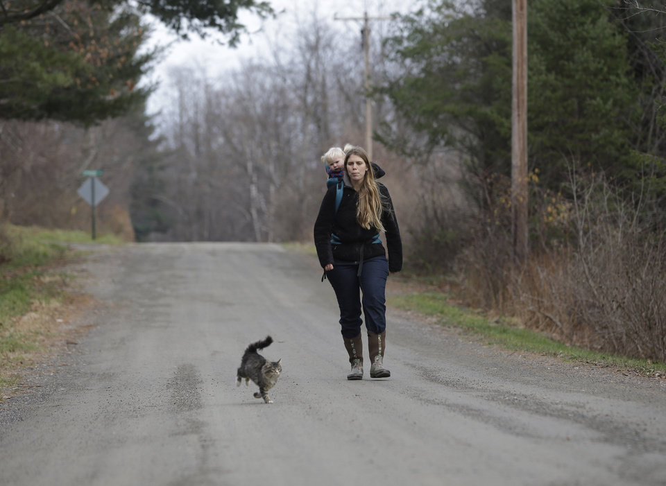 In this Thursday, Nov. 15, 2012 photo, Schuyler Gail and daughter Tillie walk on a country road at the family\'s Climbing Tree Farm in New Lebanon, N.Y. When Schuyler and husband Colby Gail were trying to get started in farming, they ran into an obstacle common to many fledgling farmers: Land was costly and hard to find. They turned to a local land conservancy, which matched them up with a landowner willing to sell for an affordable price. (AP Photo/Mike Groll)