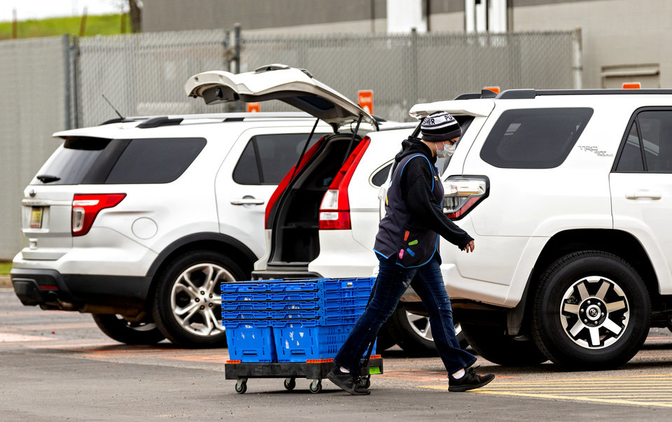 Photo - A Walmart employee finishes delivering groceries in the pickup area at the Walmart location in Yukon, Okla. on Monday, April 13, 2020.  [Chris Landsberger/The Oklahoman]