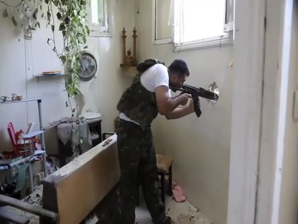 Photo -   In this image made from video and accessed Saturday, Sept. 1, 2012, a Free Syrian Army fighter fires his weapon at a Syrian Army position through a hole in an empty and destroyed home during fighting in Aleppo, Syria. Syrian troops bombarded the northern city of Aleppo Saturday with warplanes and mortar shells as soldiers clashed with rebels in different parts of Syria's largest city, activists said. The Britain-based Syrian Observatory for Human Rights said the clashes were concentrated in several tense neighborhoods where some buildings were damaged and a number of people were wounded. (AP Photo via AP video)