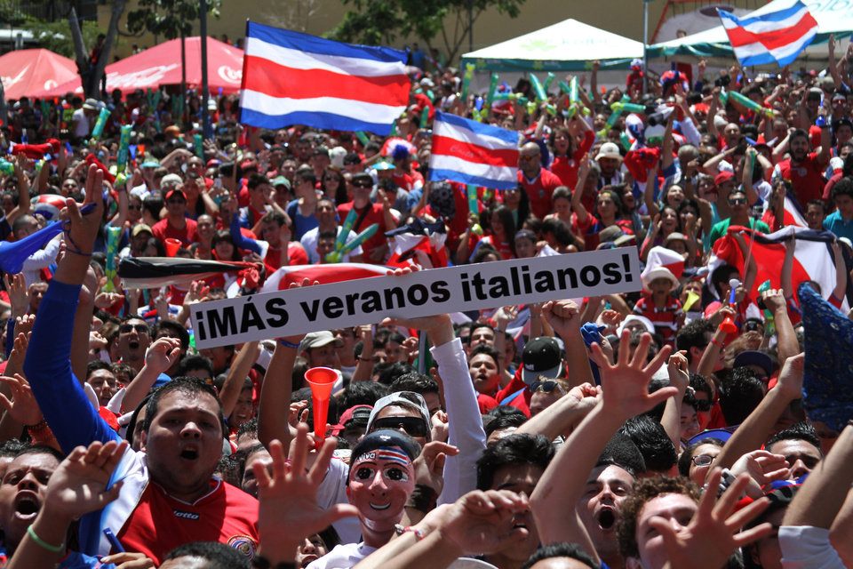 Photo - Costa Rica soccer fans celebrate after their team's World Cup victory over Italy in San Jose, Costa Rica, Friday, June 20, 2014. Costa Rica won 1-0. The sign reads in Spanish