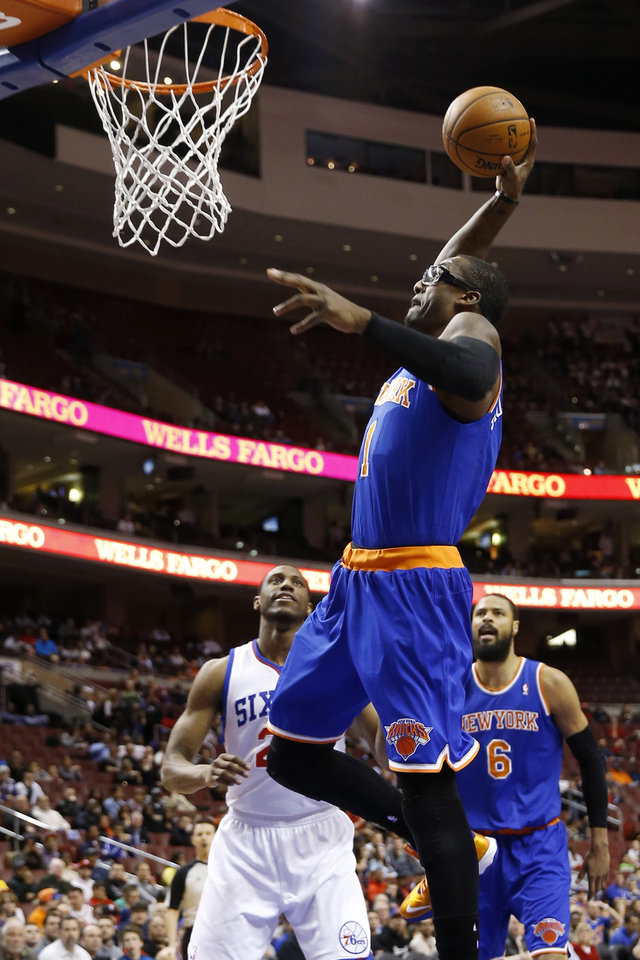 Photo - New York Knicks' Amar'e Stoudemire (1) goes up for a dunk as Philadelphia 76ers' Thaddeus Young (21) and Tyson Chandler (6) look on during the first half of an NBA basketball game, Friday, March 21, 2014, in Philadelphia. (AP Photo/Matt Slocum)