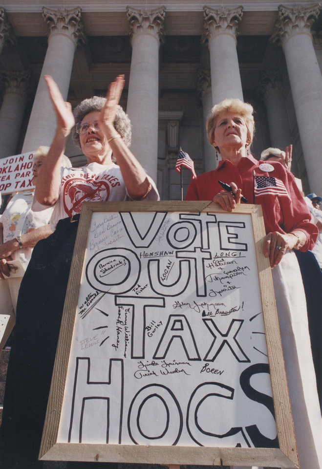 Photo - Louise Doyle, left, and Betty Burdette of Oklahoma City joined other protesters of new taxes at a rally at the state Capitol on July 16, 1990. Their sign listed names of