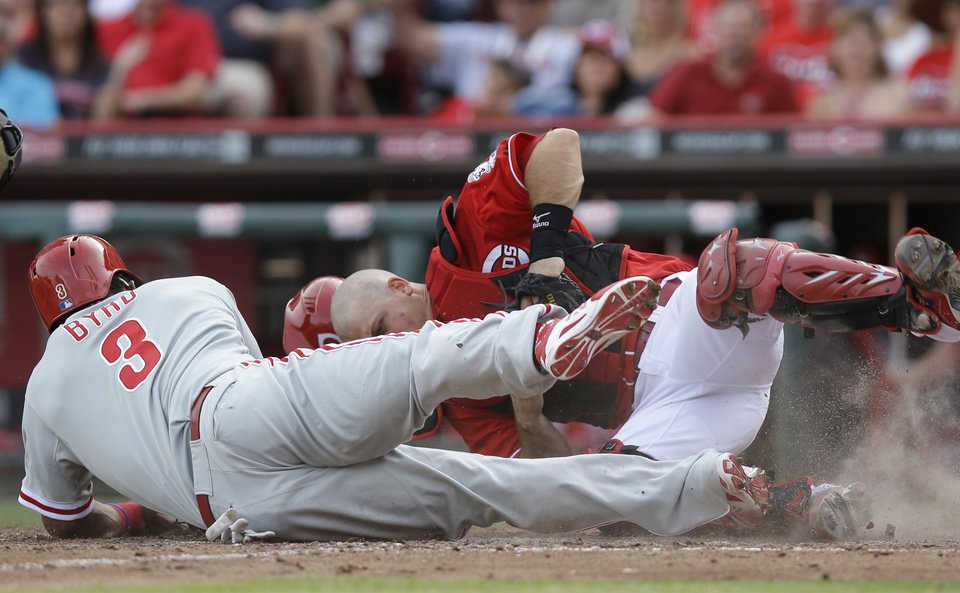 Photo - Philadelphia Phillies' Marlon Byrd (3) is tagged out at home by Cincinnati Reds catcher Devin Mesoraco in the sixth inning of a baseball game, Saturday, June 7, 2014, in Cincinnati. Byrd was trying to score on a double by Domonic Brown. (AP Photo/Al Behrman)