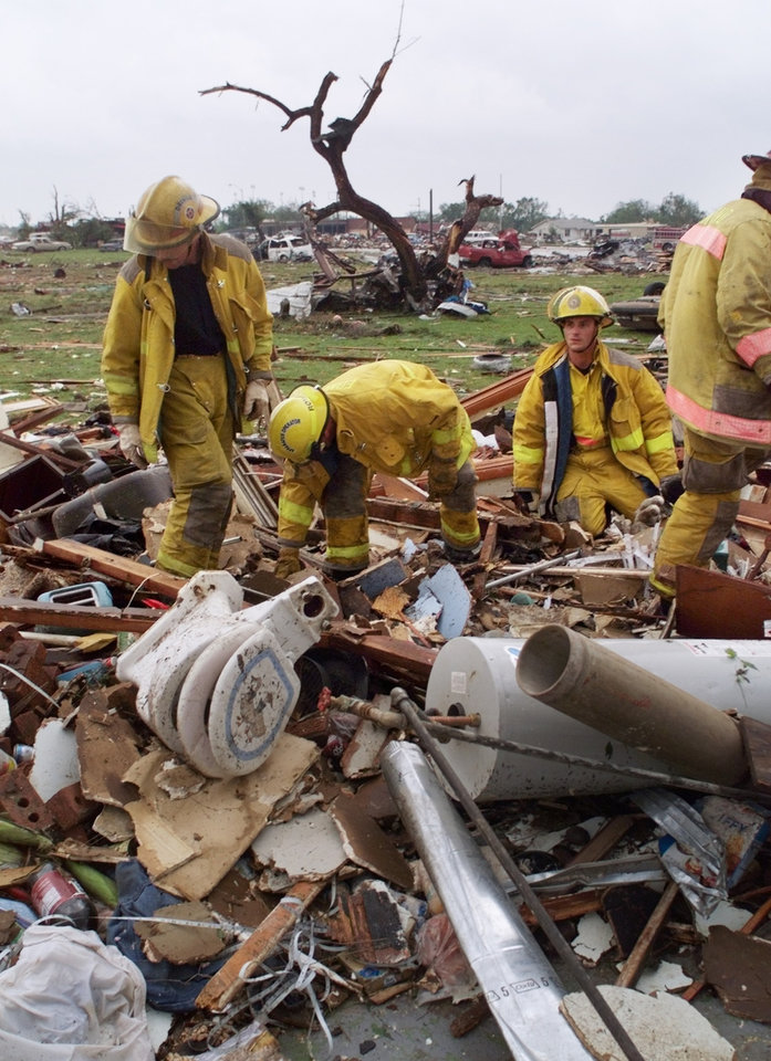 MAY 3, 1999 TORNADO: Tornado damage: Edmond Firefighters search through the remains of a home in Midwest City just East of Sooner-Rose Elementary School for survivors or bodies.