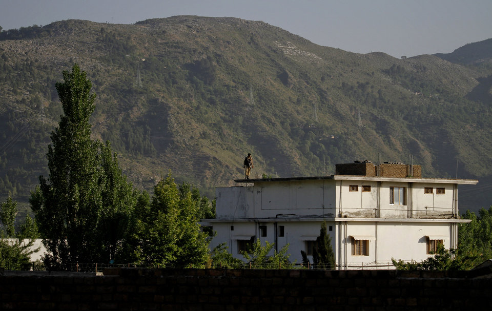 Photo - A Pakistan army soldier stands on top of the house where it is believed al-Qaida leader Osama bin Laden lived in Abbottabad, Pakistan on Monday, May 2, 2011. Bin Laden, the mastermind behind the Sept. 11, 2001, terror attacks that killed thousands of people, was slain in his hideout in Pakistan early Monday in a firefight with U.S. forces, ending a manhunt that spanned a frustrating decade. (AP Photo/Anjum Naveed) ORG XMIT: ANJ116