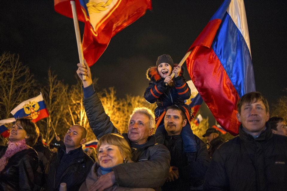 Photo - Pro-Russian people celebrate in the central square in Sevastopol, Ukraine, early Monday, March 17, 2014. Russian flags fluttered above jubilant crowds Sunday after residents in Crimea voted overwhelmingly to secede from Ukraine and join Russia. The United States and Europe condemned the ballot as illegal and destabilizing and were expected to slap sanctions against Russia for it.(AP Photo/Andrew Lubimov)