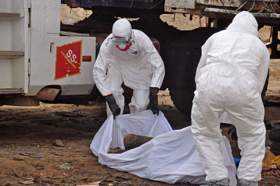 Photo - The body of a man found in the street, suspected of dying from the ebola virus is covered and removed by health workers, in the capital city of Monrovia, Liberia, Tuesday, Aug. 12, 2014. The World Health Organization declared it's ethical to use untested drugs and vaccines in the ongoing Ebola outbreak in West Africa although the tiny supply of one experimental drug handed out to three people has been depleted and it could be many months until more is available. (AP Photo/Abbas Dulleh)