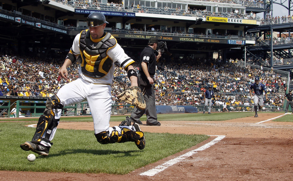 Photo - Pittsburgh Pirates catcher Chris Stewart, left, chases after a wild pitch to San Diego Padres' Yonder Alonso, allowing Seth Smith, right, to score from third in the fifth inning of the baseball game on Sunday, Aug. 10, 2014, in Pittsburgh. (AP Photo/Keith Srakocic)