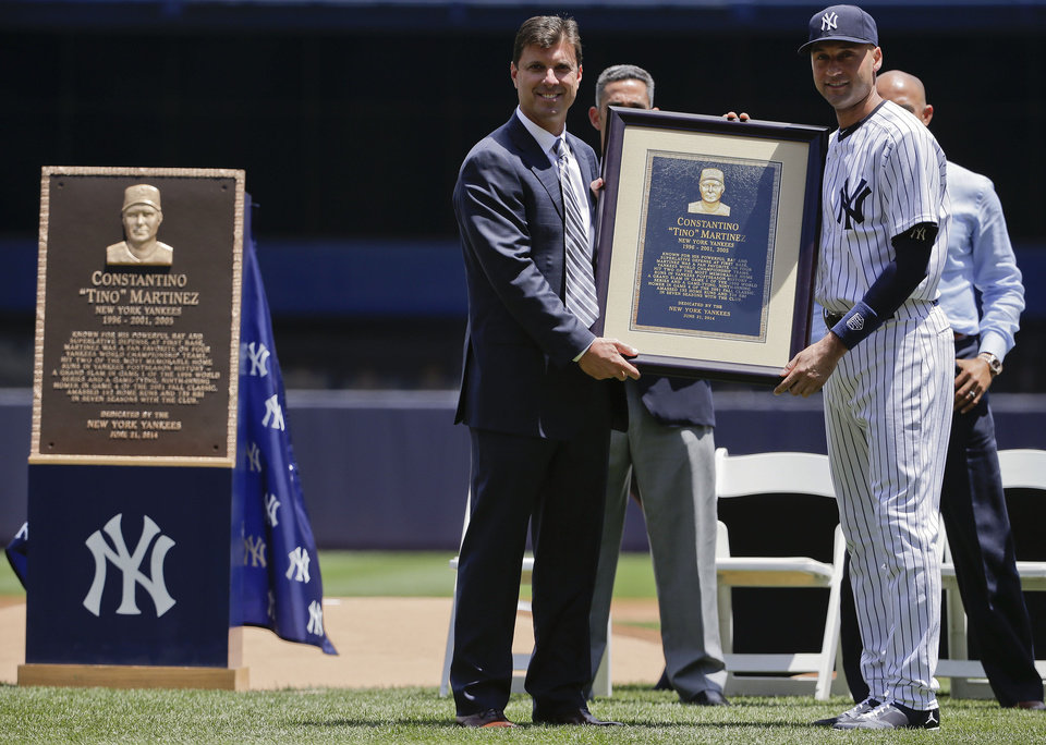 Photo - Former New York Yankees first baseman Tino Martinez, left, poses with shortstop Derek Jeter (2) and a replica of a plaque dedicated to his time with the Yankees before of a baseball game against the Baltimore Orioles, Saturday, June 21, 2014, in New York. The plaque, left, will hang at the stadium's Monument Park. (AP Photo/Julie Jacobson)