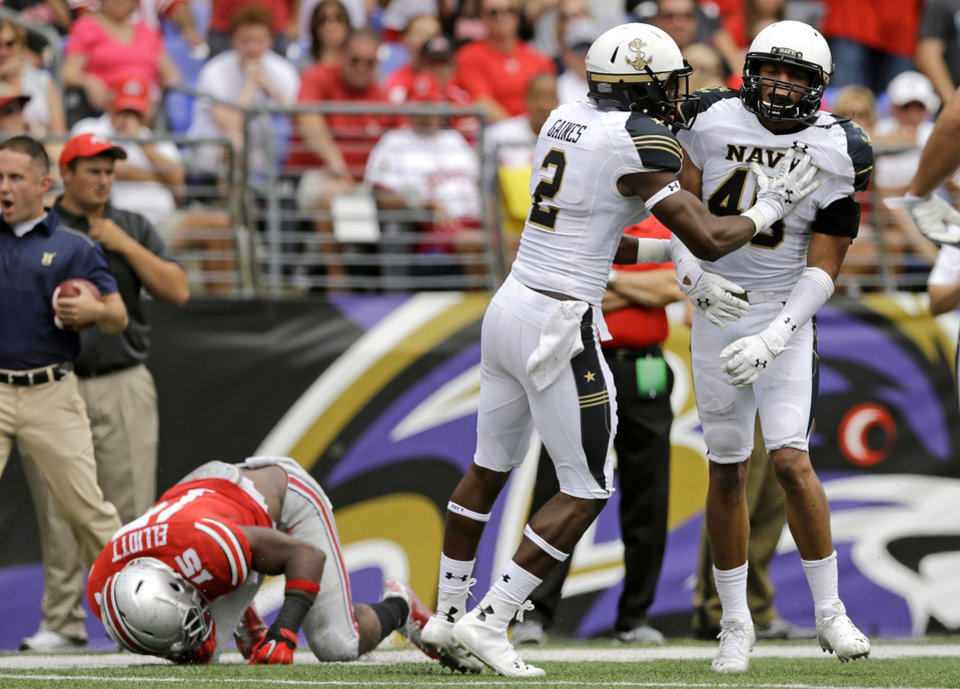 Photo - Navy safety Parrish Gaines (2) and linebacker Chris Johnson celebrate after Johnson stopped Ohio State running back Ezekiel Elliott, bottom left, on a third and goal attempt in the first half of an NCAA college football game in Baltimore, Saturday, Aug. 30, 2014. (AP Photo/Patrick Semansky)