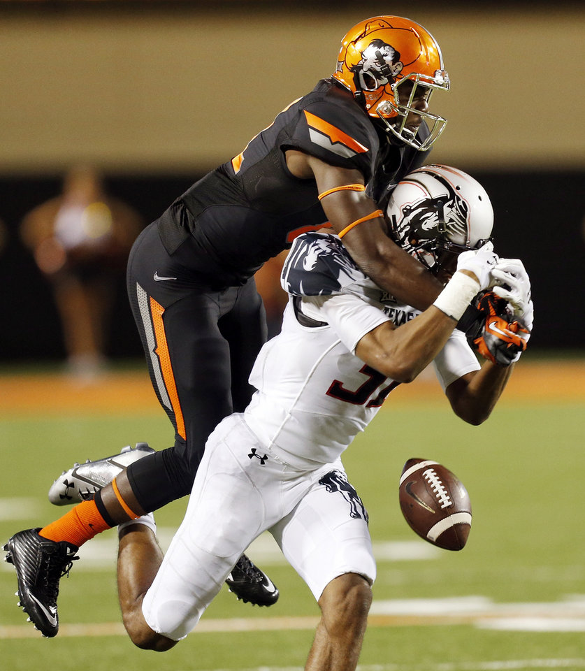 Photo - A pass intended for Oklahoma State's Jhajuan Seales (81) falls incomplete as Texas Tech's Justis Nelson (31) defends during a college football game between the Oklahoma State Cowboys (OSU) and the Texas Tech Red Raiders at Boone Pickens Stadium in Stillwater, Okla., Thursday, Sept. 25, 2014. OSU won, 45-35. Photo by Nate Billings, The Oklahoman