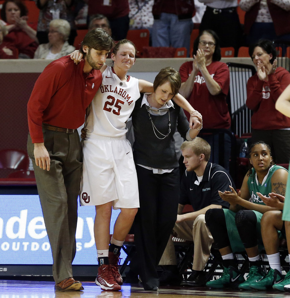Whitney Hand is helped off the court after an injury by strength coach Joseph Szendrei and trainer Carolyn Loon as the University of Oklahoma Sooners (OU) play the North Texas Mean Green in NCAA, women's college basketball at The Lloyd Noble Center on Thursday, Dec. 6, 2012  in Norman, Okla. Photo by Steve Sisney, The Oklahoman