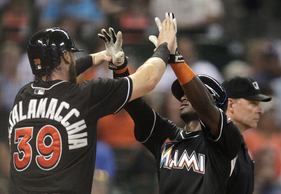 Photo - Miami Marlins Jarrod Saltalamacchia (39) celebrates with Adeiny Hechavarria after both scored on a Jeff Mathis double to left field during the seventh inning of a baseball game against the Houston Astros, Friday, July 25, 2014, in Houston. (AP Photo/Patric Schneider)