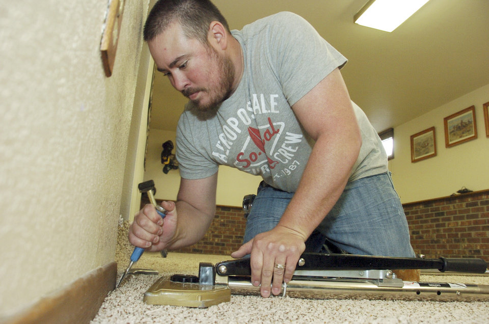 Self-employed flooring contractor Chris Folk, 33, installs carpet in a house in Billings, Mont., Friday, Nov. 2, 2012. Folk moved to Billings from Idaho with his wife and two kids when the housing crash dried up work in the Boise area, but he's been unable to sell his Idaho house and is considering declaring bankruptcy. (AP Photo/Matthew Brown)