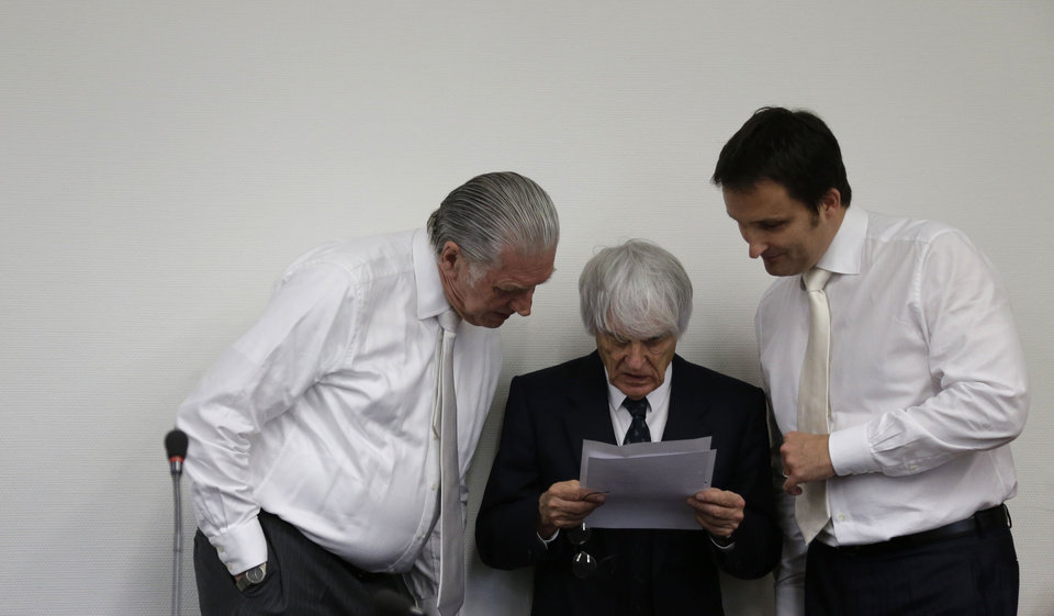 Photo - Formula One boss Bernie Ecclestone prepares for his trial  framed by his  his lawyers  Sven Thomas, left, and Norbert Scharf, right, in the regional court in Munich, southern Germany, Tuesday, July 29, 2014. Ecclestone is charged with bribery and incitement to breach of trust