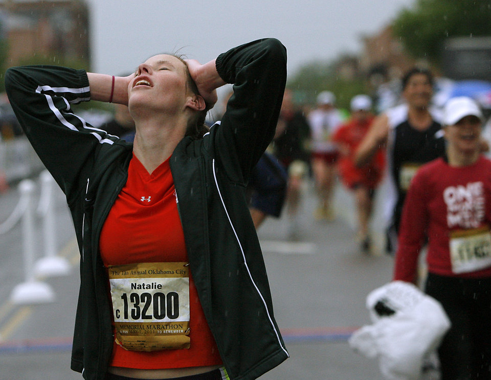 Photo - Natalie Trainor reacts as she finishes the half marathon in the rain during the 11th Annual Oklahoma City Memorial Marathon in Oklahoma City on Sunday, May 1, 2011. Photo by John Clanton, The Oklahoman