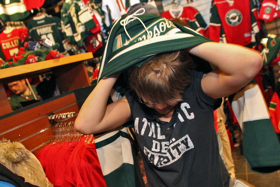 Cort Buck, 12, tries on a Minnesota Wild replica jersey as fans peruse merchandise during a one-day, 50 percent off sale in the Xcel Energy Center at an intrasquad NHL hockey game, Wednesday, Jan. 16, 2013, in St. Paul, Minn. (AP Photo/The Star Tribune, Marlin Levison) MANDATORY CREDIT; ST. PAUL PIONEER PRESS OUT; MAGS OUT; TWIN CITIES TV OUT