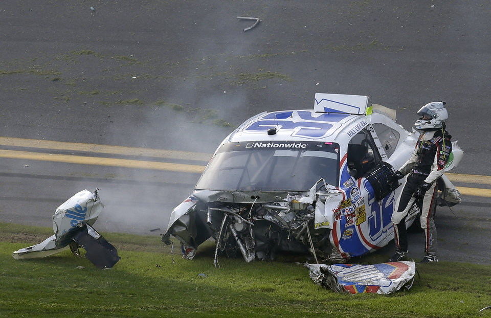 Photo - Kyle Larson climbs out of his car after being involved in a crash at the conclusion of the NASCAR Nationwide Series auto race Saturday, Feb. 23, 2013, at Daytona International Speedway in Daytona Beach, Fla. (AP Photo/Chris O'Meara)