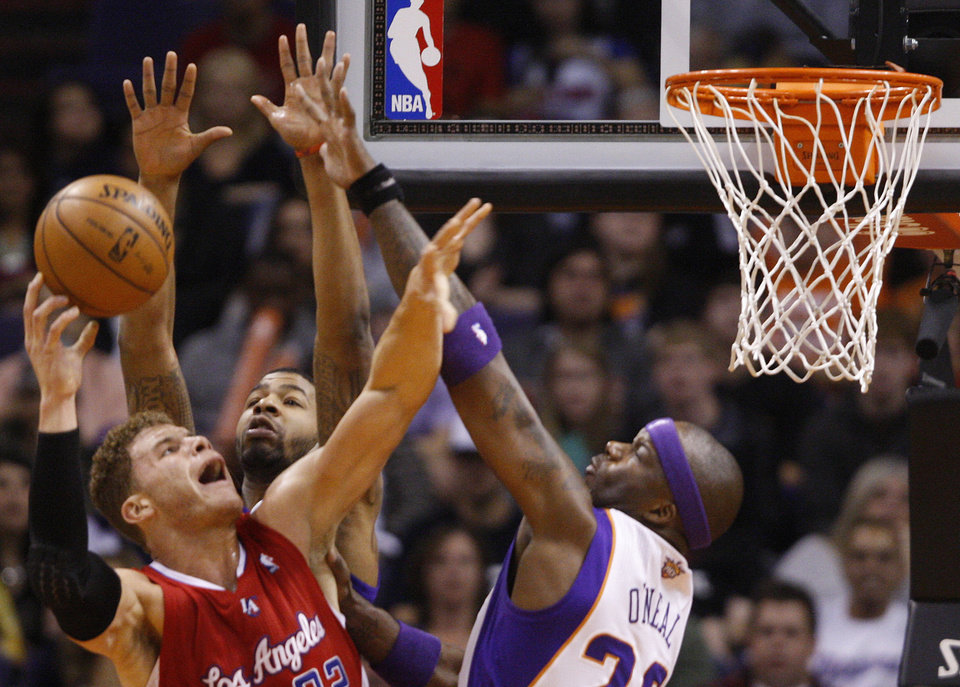 Los Angeles Clippers' Blake Griffin,left,  goes up for a basket against the Phoenix  Suns' Markieff Morris, center, and Jermaine O'Neal in the first half of an NBA basketball game at the US Airways Center in Phoenix, Ariz.,  Sunday Dec. 23, 2012.  (AP Photo/The Arizona Republic, Patrick Breen)